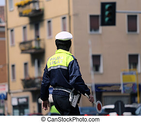 Italian policeman in uniform while blocking traffic with the...