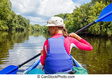 Girl kayaking - Back view of happy cute girl holding paddle...