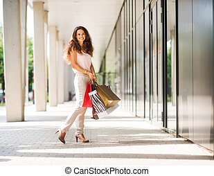 Smiling, brown-haired woman posing with colourful shopping...
