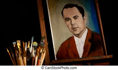 Different brushes, rotation, with easel and painting man in brown jacket,  talanted  painter or artist who takes it away on black background