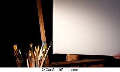 Equipment for painting, rotation wooden easel and painter puts the blank canvas on it, lot of brushes isolated, black background