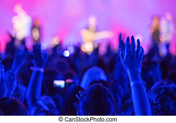 Raised Hands Concert - Open hands raised up in foreground...