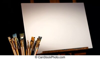 Equipment for painting, rotation wooden easel and the blank canvas on it, lot of brushes isolated, black background, dynamic change of focus