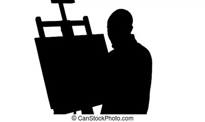 Bearded painter drawing a painting by oil paints holding the...