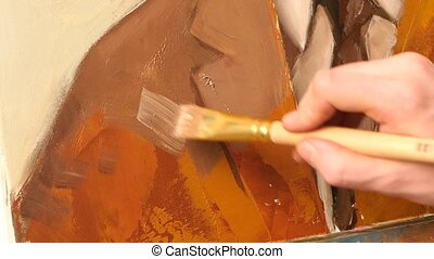 Talanted painter continues paints a picture of man`s jacket by oil paint brush with palette in his hand, on easel, white background