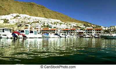 Yachts and boats in port or harbor in Los Gigantes city and...
