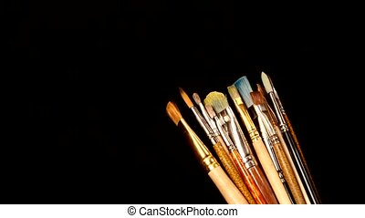 Lot of different paints and brushes on black background - A...