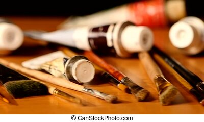 Paints and brushes, tubes of paint on wooden table, black background, cam moves to the left