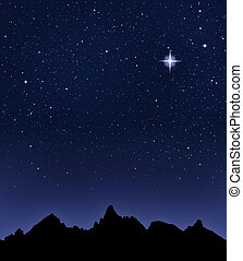 Mountain Starry Night - A mountain range silhouetted by a...