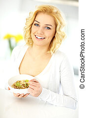 Young woman eating cereal in the kitchen