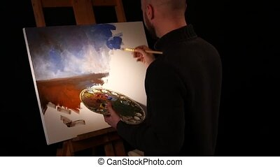 Bearded painter goes on drawing a new painting with sky and...