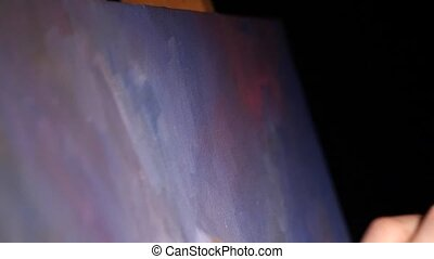 Painter makes brush strokes by oil paints on black...