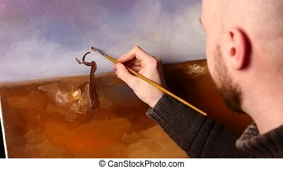 Talanted painter, dark sweater drawing an object, tree on painting by oil paints holding the palette in his hand, black background, back light, close up, slow motion