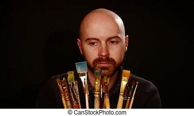 Painter choosing paintbrush among a lot of it, on black...
