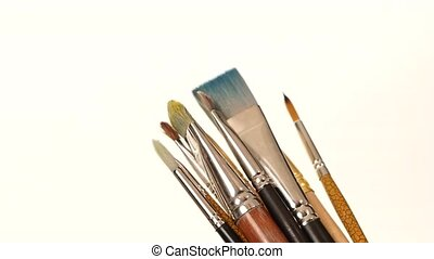 Lot of different paints and brushes on white background,...