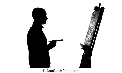 Talanted painter drawing a painting by oil paints and...