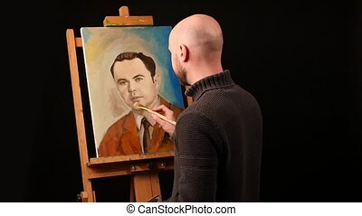Talanted artist paints a picture, man, of oil paint brush with palette in his hand, on brown easel, black background, slow motion