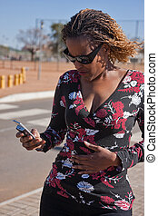 woman street phone - African woman using her phone in the...