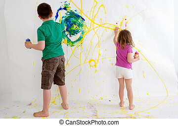 Two young children freehand painting on a wall - Two young...
