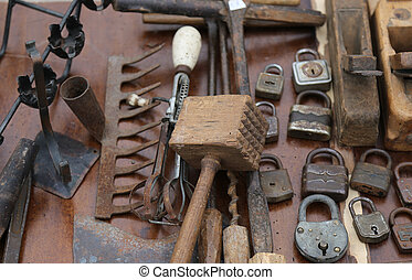 hammer and rusty padlocks and planers in the workshop of flea market