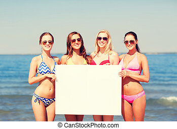 group of smiling women with blank board on beach - summer...