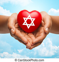 close up of hands holding heart with jewish star - religion,...