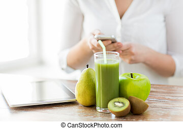 close up of woman with smartphone and fruits - healthy...