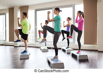 group of people working out with steppers in gym - fitness,...