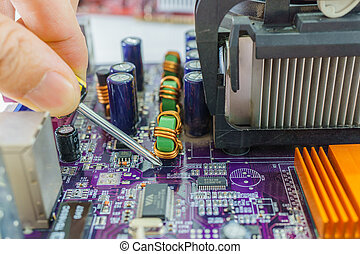 Technician's hands fixing mainboard with screwdriver - close...