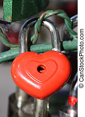 Red heart lock hanging on metal fence