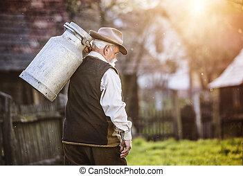Farmer with milk kettle - Senior farmer carrying kettle for...