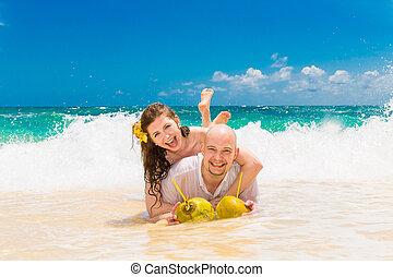 Happy bride and groom having fun on a tropical beach Wedding...