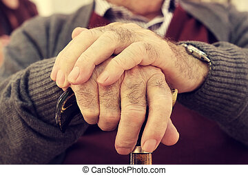 old man with a walking stick - closeup of the hands of an...