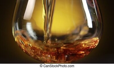 Cognac pouring from bottle into glass with splash on yellow background. Close up.
