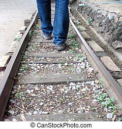 man walking in sandals across train tracks