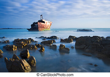 Old shipwreck long exposure on rocks at sunset