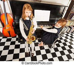 Girls playing on the alto saxophone and piano