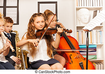 Group of kids playing musical instruments indoors