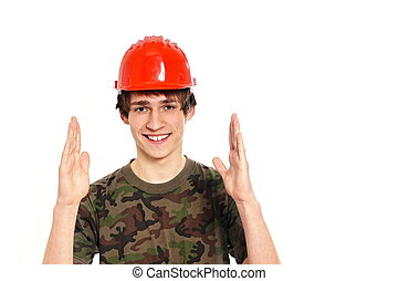 Smiling young man in protective helmet shows size, right you...