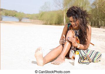 young woman applying suncream