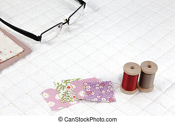 accessory needlework put on white patchwork Quilt background