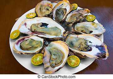 Opened fresh oysters in a white plate with lime on a wooden...