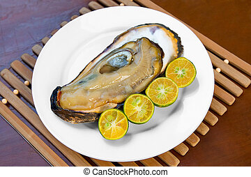 Opened fresh oyster in a white plate with lime on a wooden...