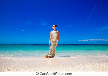 Young beautiful girl in gold dress on the beach of a tropical island. Summer vacation concept.
