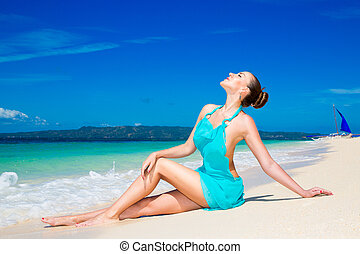 Young beautiful girl in blue dress on the beach of a tropical island. Summer vacation concept.