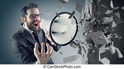 Young businessman crushing concrete wall with a megaphone -...