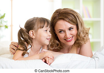 mom with daughter converse lying on bed at home