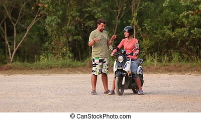 instructor explains right way of driving scooter to girl