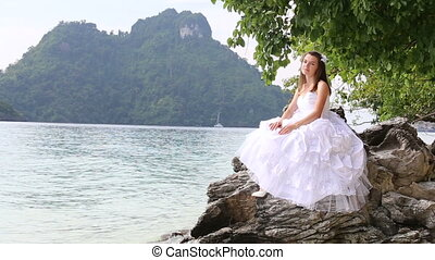 longhaired bride sits on rock under tree against sea and island
