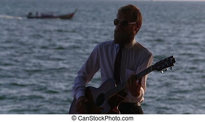 guitarist in shirt plays against sea and longtail boats -...